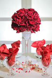 Roses arrangement and glasses. Elegant red roses flower arrangement and napkins in glasses on a table Royalty Free Stock Images