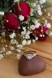 Roses avec Diamond Ring sur le chocolat de coeur Photographie stock libre de droits