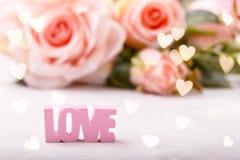 Roses roses avec le mot AMOUR image stock