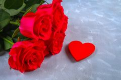Roses roses avec les bougies rouges sous forme de coeur sur un fond gris Calibre pour le 8 mars, le jour de mère, Saint-Valentin Photographie stock libre de droits