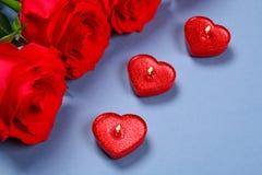Roses roses avec les bougies rouges sous forme de coeur sur un fond gris Calibre pour le 8 mars, le jour de mère, Saint-Valentin Image libre de droits