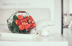 Roses in basket on a table. A bouquet of roses in a basket on the table in a bright white room interior stock image