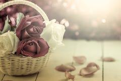 Roses in basket on wooden background  in vintage color Stock Images
