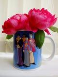 Roses in a beatles mug. Dark pink roses in a beatles mug royalty free stock images