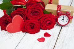Roses. Beautiful bouquet of roses with a gift box on a wooden background Stock Photography