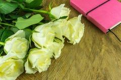 Roses blanches avec des feuilles vertes et un bloc-notes Images stock