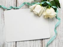 Roses blanches avec la carte de voeux Image stock