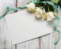 Roses blanches avec la carte de voeux Photographie stock