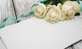 Roses blanches avec la carte de voeux Images stock