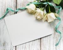 Roses blanches avec la carte de voeux Photos stock