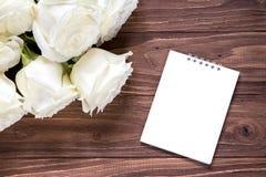 Roses blanches avec le livre blanc vide sur la table en bois Papier peint romantique original pour le bureau Images stock