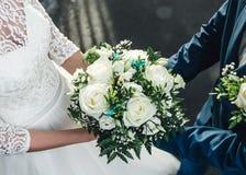 Roses blanches dans des mains des jeunes mariés Image pour épouser des blogs, cartes de voeux Images libres de droits