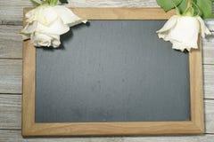 Roses blanches sur une ardoise grise Photographie stock libre de droits