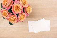 Roses and blank cards top. Top view of beautiful roses and blank cards on wooden desktop. Mock up Stock Photography