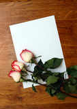 Roses and blank paper on table Royalty Free Stock Photos
