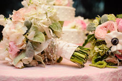 Roses bouquet wrapped in ribbon in front of wedding cake. Wedding roses in a bouquet wrapped in ribbon and a roserie in front of a cake Royalty Free Stock Image