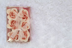 Roses candles. Beautiful roses candles and gift box on a white background. Soft fluffy white veil Royalty Free Stock Image