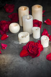 Roses and candles. Romantic composition of the petals of roses and candles. Dark, shabby background Stock Image