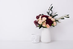 Roses and carnations in a vase in white interior. Beautiful bouquet of roses and carnations in a vase in white interior with copyspace. Elegant home decor royalty free stock photos