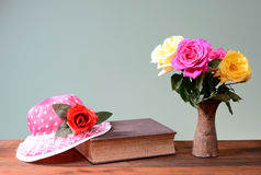 Roses in a ceramic vase, a book and a hat Royalty Free Stock Image