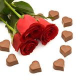 Roses and chocolate. Red roses and heart shaped chocolate stock image