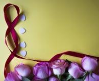 Roses roses, coeurs blancs et ruban sur le fond jaune Fond de jour de valentines photo stock