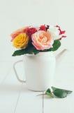 Roses colorées dans le pot blanc de café d'émail Photo stock
