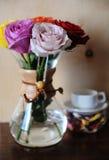 Roses colorées dans un pot de café et une tasse blanche sur un support avec le flowerson sec sur le fond en bois Images libres de droits