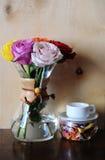 Roses colorées dans un pot de café et une tasse blanche sur un support avec le flowerson sec sur le fond en bois Photo stock