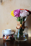 Roses colorées dans un pot de café et une tasse blanche sur un support avec le flowerson sec sur le fond en bois Photographie stock