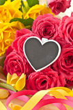 Roses colorées et un petit tableau noir Image stock