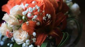 Roses crèmes, lis oranges et fleurs blanches minuscules, détails du bouquet de mariage Photos stock