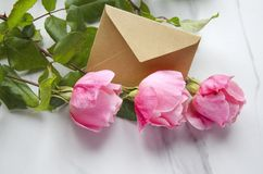 Roses and a craft envelope as a symbol of valentines day stock image