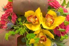 Roses roses, cymbidium jaune, mamans vertes, et paumes dans un tropique Image stock