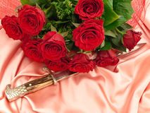 Roses and dagger. Dagger near the red beautiful roses on a pink silk fabric Royalty Free Stock Images