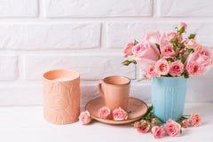 Roses roses dans la tasse bleue, la bougie brûlante et peu de tasse pour le coffe Photo stock