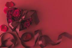 Roses dans le boîte-cadeau en forme de coeur avec le ruban et des pétales d'isolement sur le rouge, concept de vacances de jour d Images libres de droits