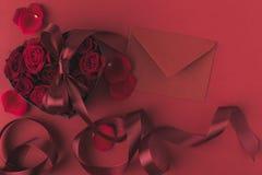 Roses dans le boîte-cadeau en forme de coeur avec le ruban et l'enveloppe sur le rouge, concept de vacances de jour de valentines Photos libres de droits
