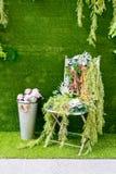 Roses roses dans le seau en métal et la chaise de décoration sur le GR artificiel Images stock