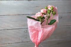 Roses dans un vase avec l'enveloppe sur le fond gris en bois photo stock