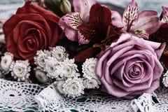 Roses de bouquet et vieilles lettres sur le bureau en bois dans un style de vintage Photographie stock