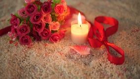 Roses de bouquet, ruban et longueur brûlante de bougie pour le Saint Valentin banque de vidéos