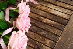 Roses de floraison roses sur le bois Photos stock