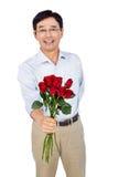 Roses de offre d'homme asiatique plus âgé Photos stock