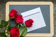 Roses de Valentine avec la lettre sur le tableau noir Photographie stock libre de droits
