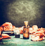 Roses essential oil in bottle on rustic vintage background, top view , place for text Stock Image