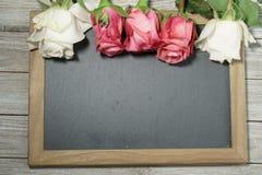 Roses roses et blanches sur une ardoise grise Photo stock