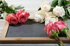 Roses roses et blanches sur une ardoise grise Photographie stock
