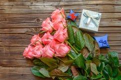 Roses et boîte-cadeau au-dessus de vieux fond en bois Photo stock