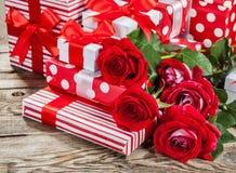 Roses et boîtes avec des cadeaux sur le conseil image libre de droits